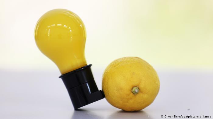 Eine gelbe Glühbirne und eine Zitrone, verbunden mit einem Stecker.