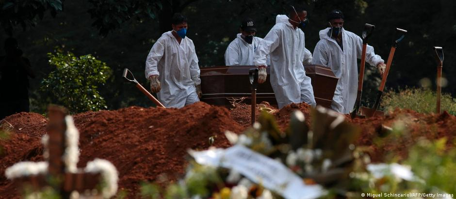 Cemetery workers carry a coffin.