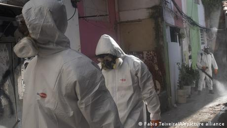Workers in protective suits disinfect a low-income community in Rio de Janeiro