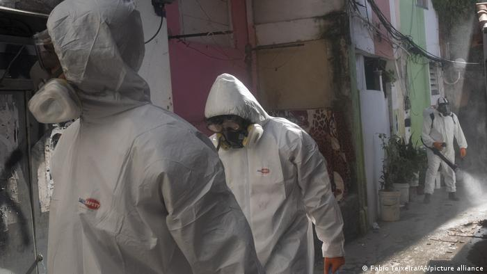 Total de vítimas da doença no Brasil supera 307 mil. Funcionarios da saúde desinfetam calçadas no morro Dona Marta, no Rio de Janeiro