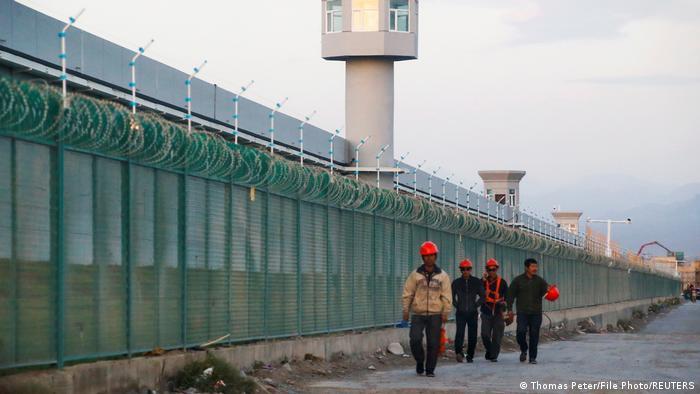 Pekerja berjalan di sepanjang pagar perimeter pusat pendidikan ulang di Xinjiang