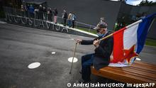 An admirer wearing a protective mask holds a Yugoslavia flag as he sits on a bench in front of the late former President of communist Yugoslavia Josip Broz Tito (18921980) memorial complex, in Belgrade on May 25, 2020. - Groups of people flocked to Tito's memorial complex to mark his 128th birthday. People in small groups have been allowed to enter the complex respecting all preventive measures against the spread of the novel coronavirus, COVID-19, pandemic. (Photo by Andrej ISAKOVIC / AFP) (Photo by ANDREJ ISAKOVIC/AFP via Getty Images)