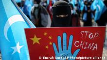 A protester from the Uyghur community living in Turkey holds up an anti-China placard during a protest against the visit of China's Foreign Minister Wang Yi to Turkey on March 25, 2021