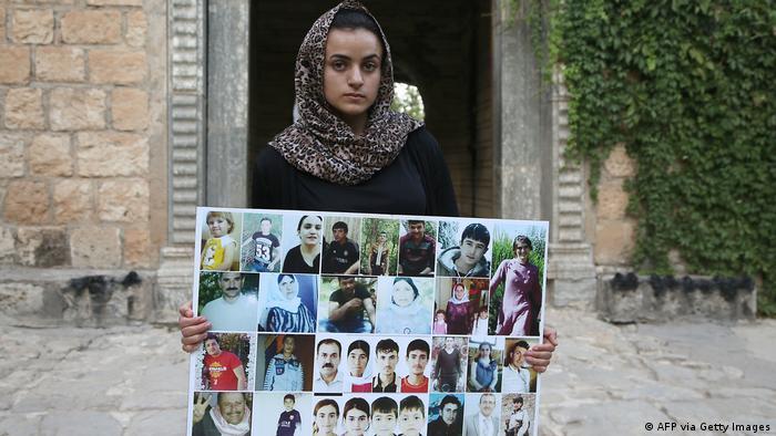 مرأة أيزيدية تحمل صوراً لضحايا من قريتها بالقرب من سنجار