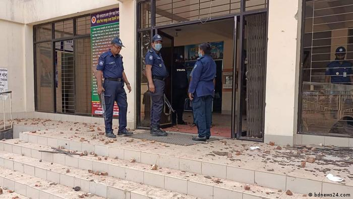 Three police officers stand in front of a building entrance that appears to have been attacked by stones.