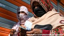 A woman (R) counts rupee notes after collecting cash of financial assistance through a mobile wallet under the governmental Ehsaas Emergency Cash Programme for families in need during a government-imposed nationwide lockdown as a preventive measure against the COVID-19 coronavirus, in Islamabad on April 9, 2020. (Photo by Aamir QURESHI / AFP) (Photo by AAMIR QURESHI/AFP via Getty Images)