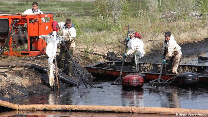 Men cleaning an oil spill from a river