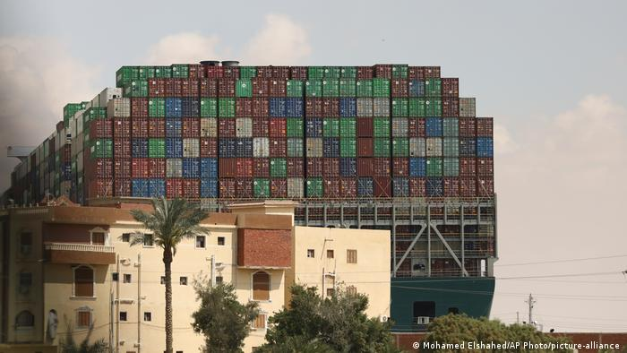 The container ship Ever Given looms over a building next to the waterway