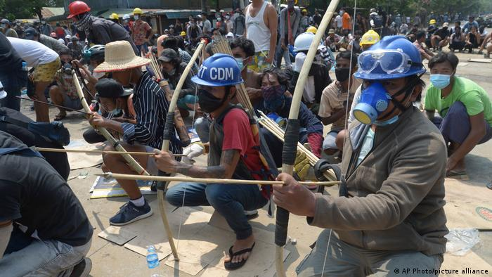 Anti-coup protesters prepare makeshift bow and arrows to confront police in Thaketa township, Yangon