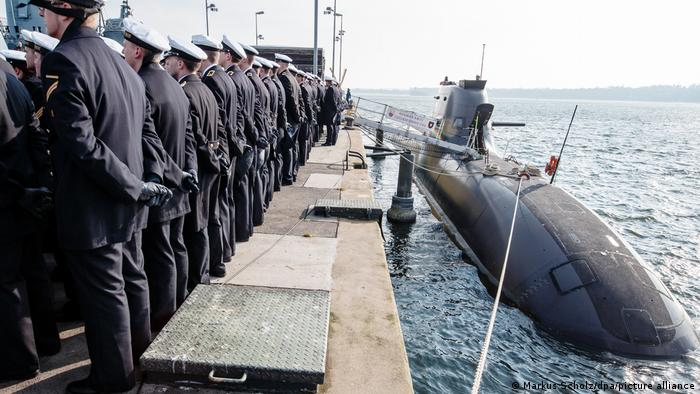 German naval officers stand in a line on a dock next to a U35 submarine