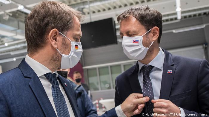 Eduard Heger coloca la corbata de Igor Matovic en una imagen reciente.