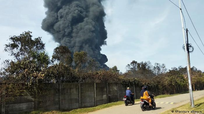 Motorists ride past as thick smoke billows from a fire that razes through Pertamina Balongan Refinery