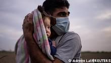 Francisco, 34, an asylum seeking migrant from Honduras, cradles his nine month old daughter Megan from the early morning cold and wind, as they await for transport to a processing centre after crossing the Rio Grande river into the United States from Mexico on a raft in La Joya, Texas, U.S., March 25, 2021. Over 750 migrants crossed into the U.S. from Mexico in La Joya and nearby areas early morning on March 25, agents on the scene said, and slept along a border road next to farmland for hours before being transported to a U.S. border patrol processing facility. REUTERS/Adrees Latif TPX IMAGES OF THE DAY