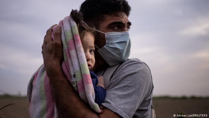 Foto simbólica de un migrante con mascarilla que abraza a un bebé.