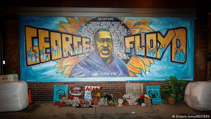 A graffiti artwork on a brick wall shows George Floyd's face and his name as large-scale lettering, as well as the names of other African-American victims of police violence in the US. In front of the painting are objects and protest signs left by mourners.