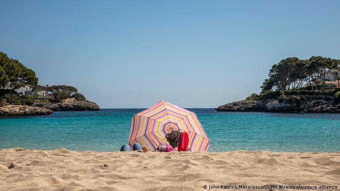 Spain, Mallorca: people under a parasol on an empty beach