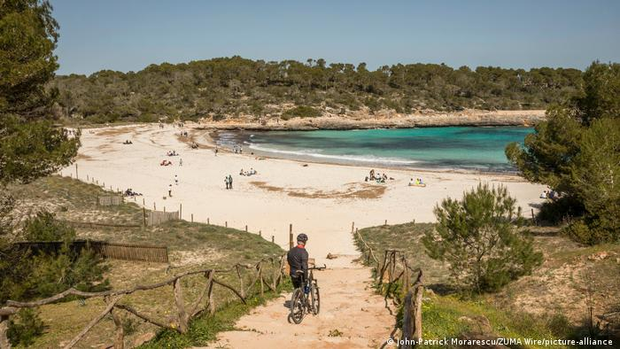 The rather empty beach of Cala Mondrago on Mallorca with a few people sitting on the beach enjoying a sunny day