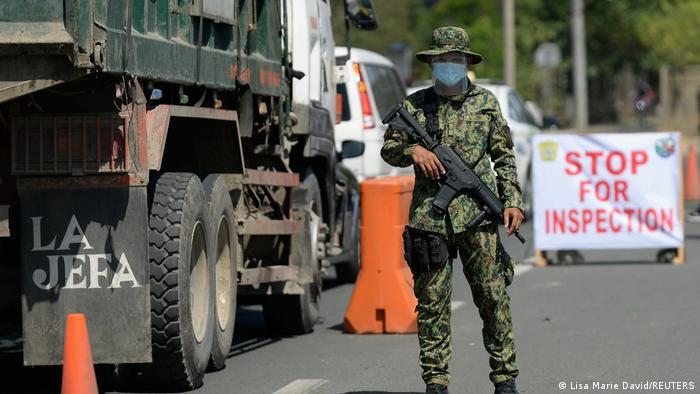 Soldat mit automatischer Waffe sichert einen Checkpoint an einer Straße in Manila, Philippinen