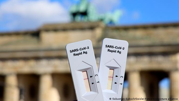 Two rapid antigen tests held up against the backdrop of the Brandenburg Gate