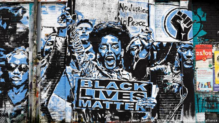 On the wall of a building in Cologne, activists raise their fists in a black and blue painting and hold a Black Lives Matter sign.