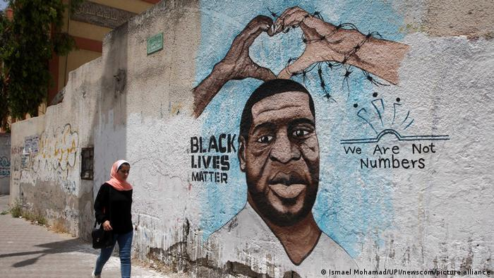 On a sunny day in Gaza City, a woman in a pink headscarf and jeans walks past a portrait of George Floyd, the slogans We Are Not Numbers and Black Lives Matter.
