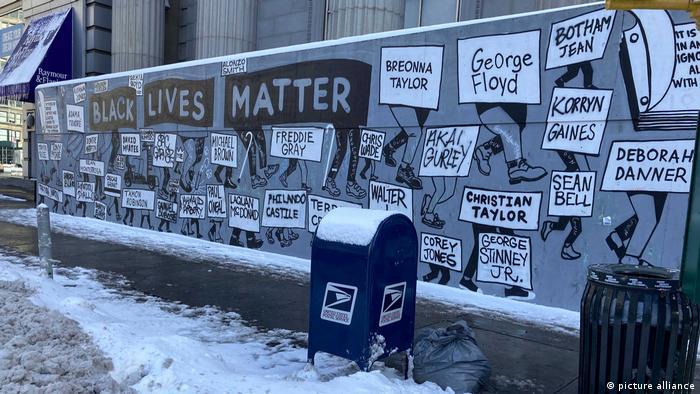 Auf dem verschneiten Union Square in New York City prangt ein grau-schwarz-weißes Wandgemälde hinter einem blauen Briefkasten, auf dem der Schriftzug Black Lives Matter sowie die Namen derer zu lesen sind, die Opfer von Polizeigewalt geworden sind.