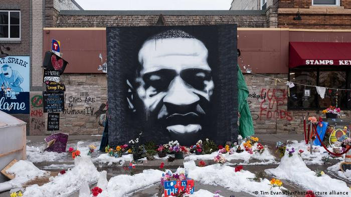 A black and white mural of George Floyd's face. In front of it, mourners have laid bouquets of flowers.