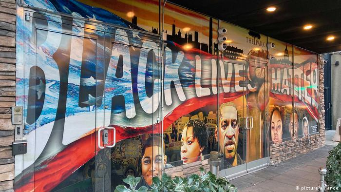 A mural in Washington, DC.: A black fist holds up a U.S. flag that reads Black Lives Matter.
