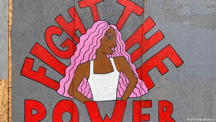 Diese Streetart zeigt eine schwarze Frau mit pinkem, langen Haar. Um sie ist der Schriftzug Fight the Power in rot angeordnet.