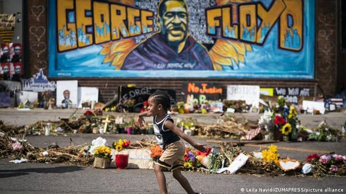 Graffiti mit George Floyd, davor Kerzen und Blumen und ein rennendes Kind