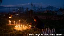 A Kashmiri Shiite Muslim girl lights candles at the grave of her relative to mark Shab-e- Barat, on the outskirts of Srinagar, Indian controlled Kashmir, Monday, March 29, 2021. Muslims visit ancestral graveyards for the salvation of the souls of the departed and also believe that all sins will be forgiven by praying to Allah throughout the Shab-e Barat night. (AP Photo/ Dar Yasin)