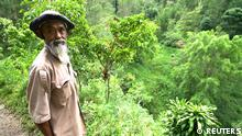 Sadiman, a 69-year-old ecowarrior, stands near a hill which is the first area he replanted with trees 20 years ago, in Wonogiri, Central Java province, Indonesia, in this still taken from March 13, 2021 video. Stringer/REUTERS TV via REUTERS. NO RESALES. NO ARCHIVES.