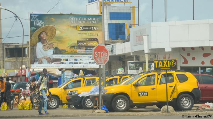 A man walks past lined up taxis in Cotonou