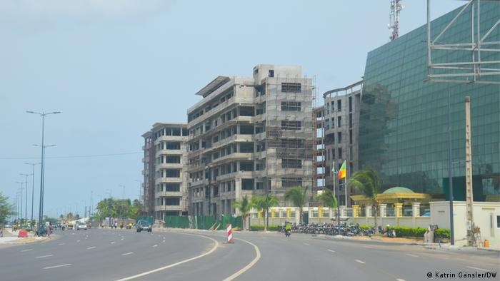 A modern building next to unfinished houses