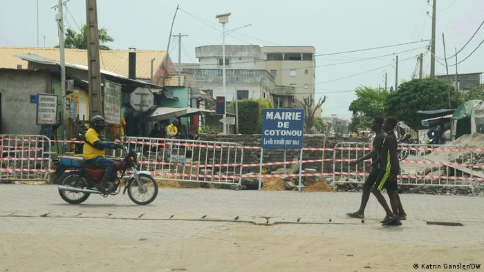 Two people and one man on a motor bike pass a blocked off construction site in Cotonou