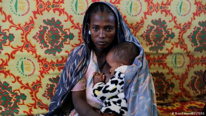 A woman holds an infant inside the Adiha secondary school