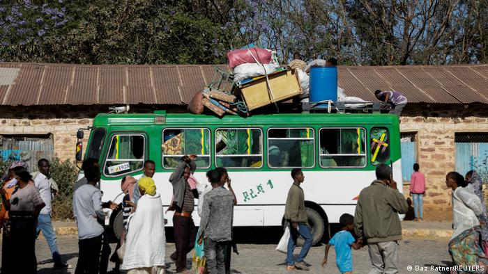 A bus carrying displaced people arrives at the Tsehaye primary school