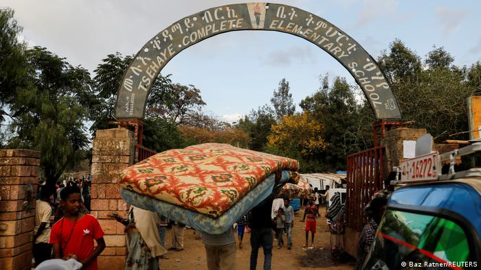 A man carries a mattress into the Tsehaye primary school