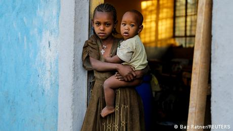 Asmara, 11, holds her one-year-old brother Barakat at the doorway to a classroom now used as their living space, at the Tsehaye primary school