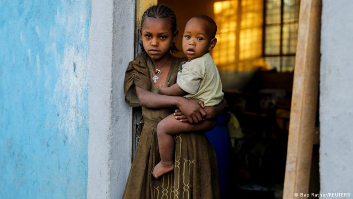 An 11-year-old girl holding her little brother in a classroom in Tigray, Ethiopia
