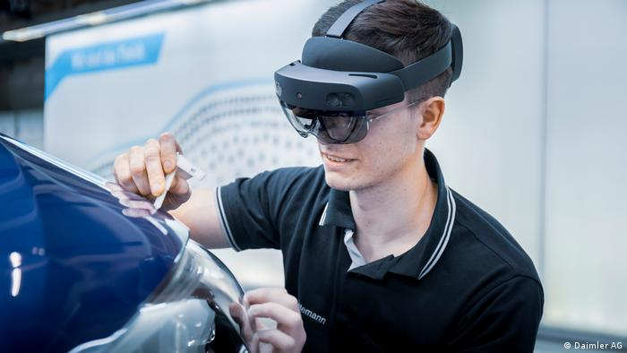 A mechanic at Merzedes-Benz wearing augmented reality glasses while repairing a car