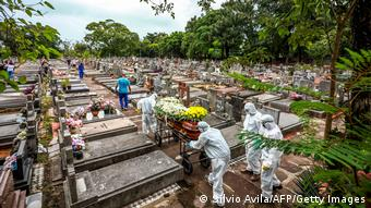 Мужчины в защитной одежде на кладбище в Порту-Алегри