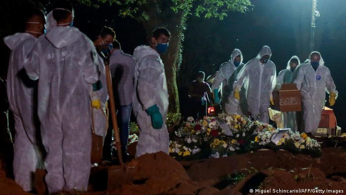 Funcionários com trajes de proteção trabalham em enterros à noite em cemitério de São Paulo. Taxa de mortalidade por grupo de 100 mil habitantes no Brasil subiu para 179,9