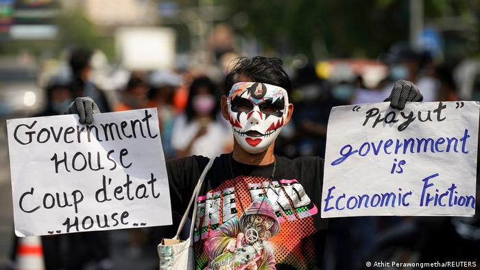 Anti-government protester holds sign saying Prayut government is economic friction