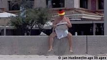 """*** Dieses Bild ist fertig zugeschnitten als Social Media Snack (für Facebook, Twitter, Instagram) im Tableau zu finden: Fach """"Images"""" —> Weltspiegel/Bilder des Tages *** +++29.03.2021+++ News Bilder des Tages 29.03,2021,xlakx,Mallorca erste Touristen aus Deutschland eingetroffen emspor,ein maennlicher Tourist mit Deutschland Muetze liest auf einer Mauer eine Tageszeitung.Model Release vorhanden Palma in Mallorca *** 29 03,2021,xlakx,Mallorca first tourists from Germany arrived emspor,a male tourist with Germany hat reads a daily newspaper on a wall Model release present Palma in Mallorca"""