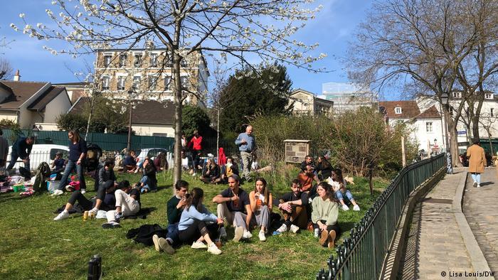 Des gens assis sur une pelouse à Paris (Photo: Lisa Louis)