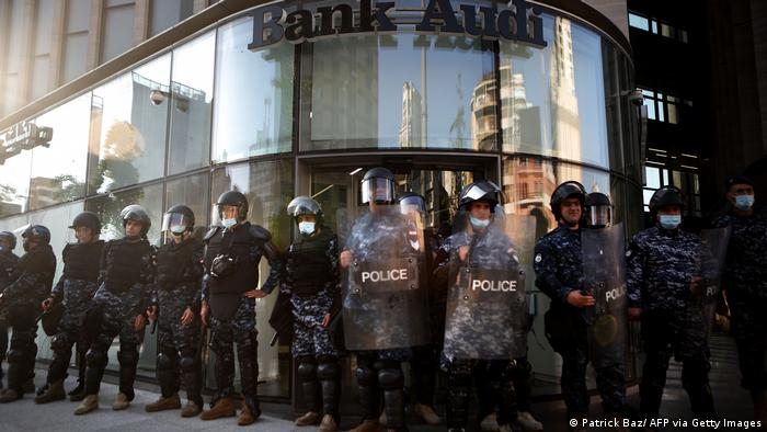 A row of Lebanese riot police guard a bank in the capital, Beirut