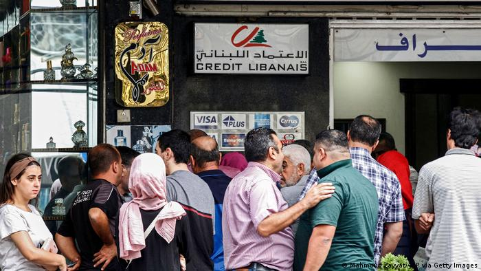 People queue outside an automatic teller machine (ATM) at a bank in the southern Lebanese city of Sidon