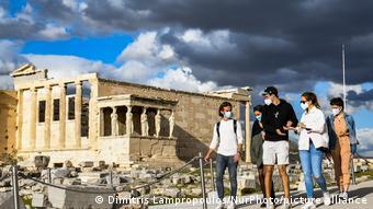 Люди в медицинских масках около Акрополя в Афинах