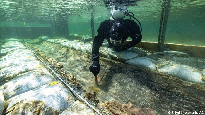 A diver examines the submerged dugout canoe